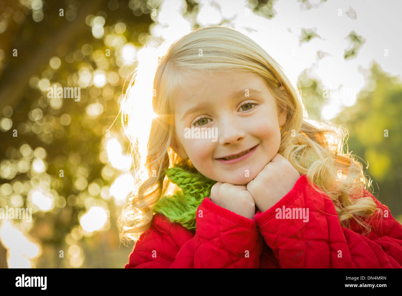 Sweet Little Girl Wearing Winter Coat and Scarf Outdoors at the Park. - Stock Image