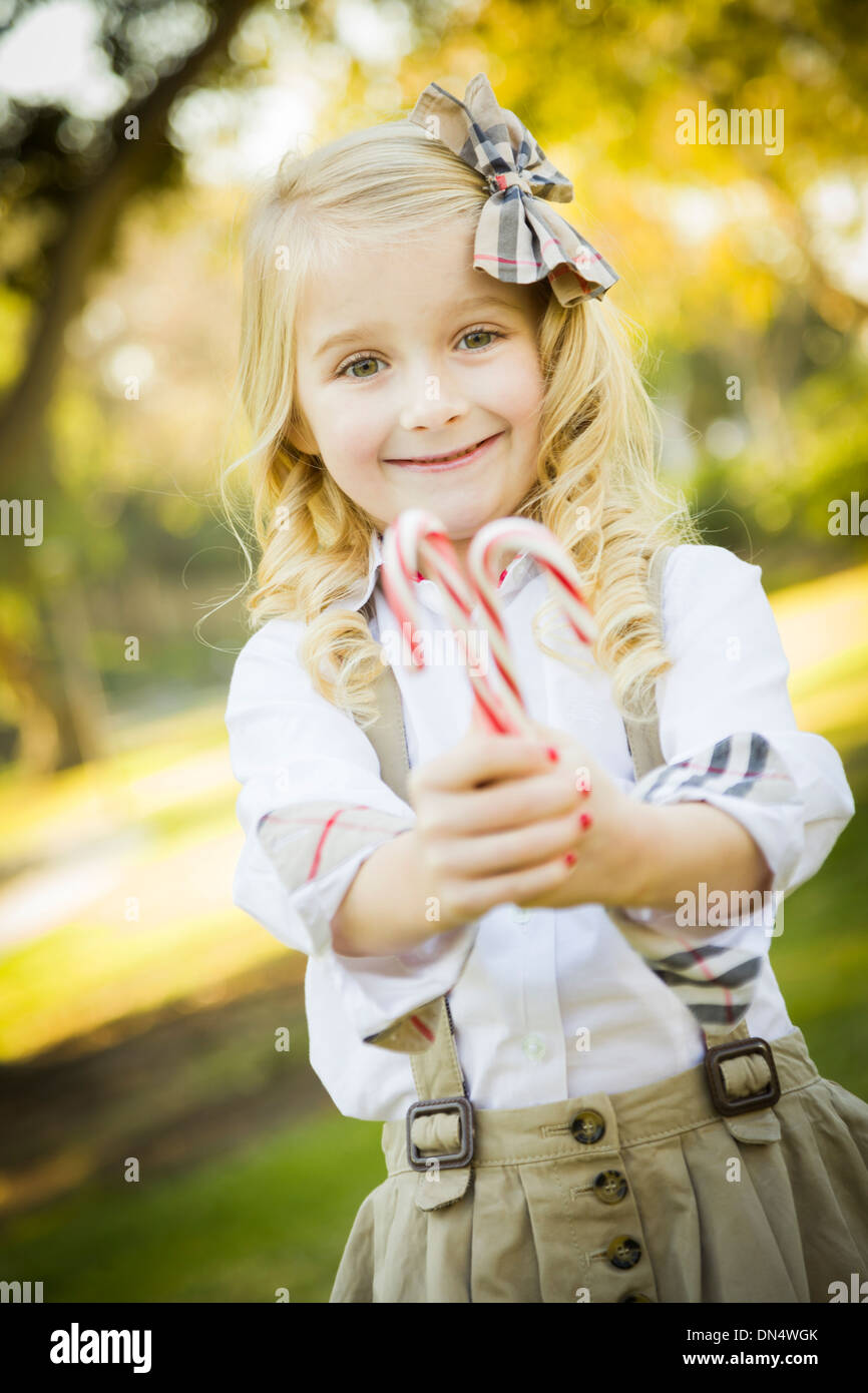 d68d47967c2 Cute Little Girl with a Bow in Her Hair Holding Her Christmas Candy Canes  Outdoors.