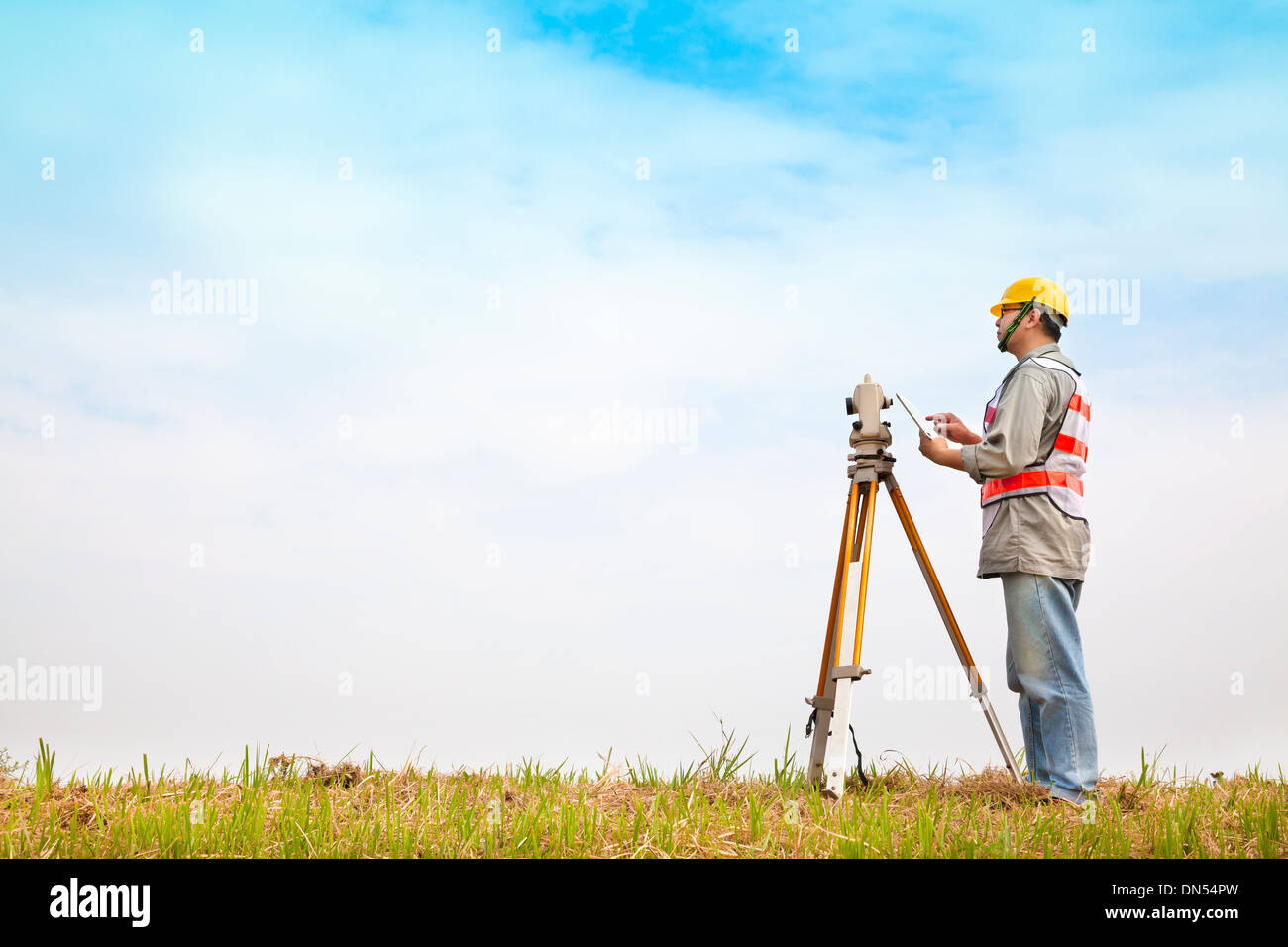 Surveyor engineer making measure on the field with tablet pc - Stock Image