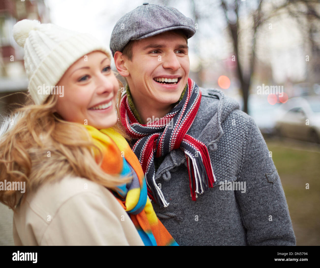 Image of affectionate couple looking at something and laughing outside - Stock Image