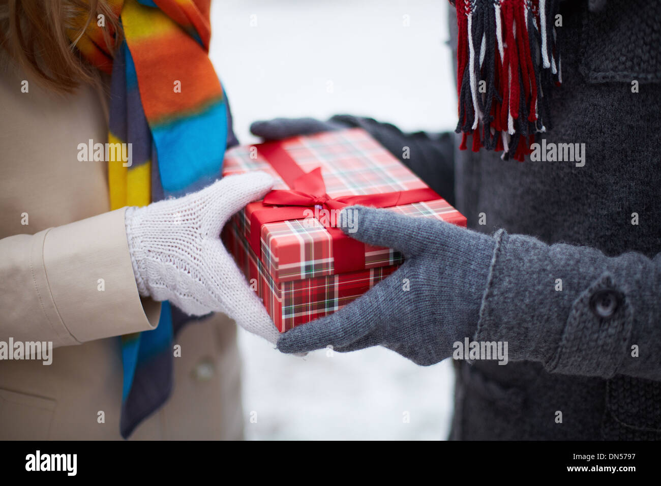 Image of gloved hand of guy giving his girlfriend Christmas present - Stock Image