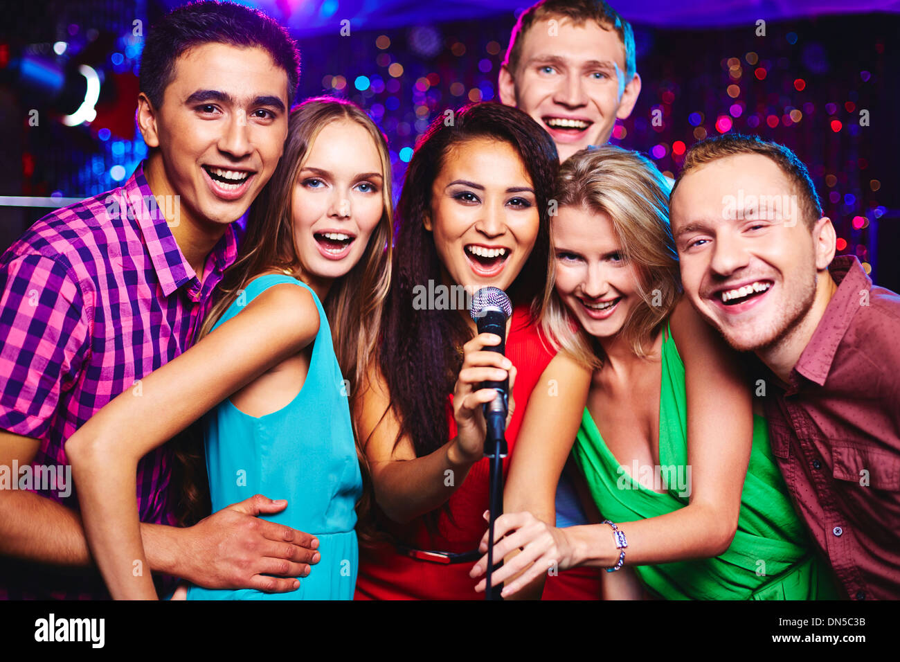 Portrait of happy girls and guys singing in microphone in the karaoke bar - Stock Image
