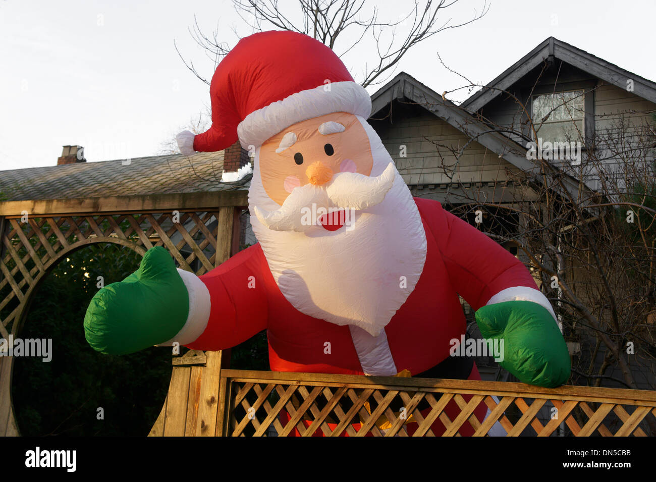 Giant inflatable Santa Claus balloon in the front yard of a house - Stock Image