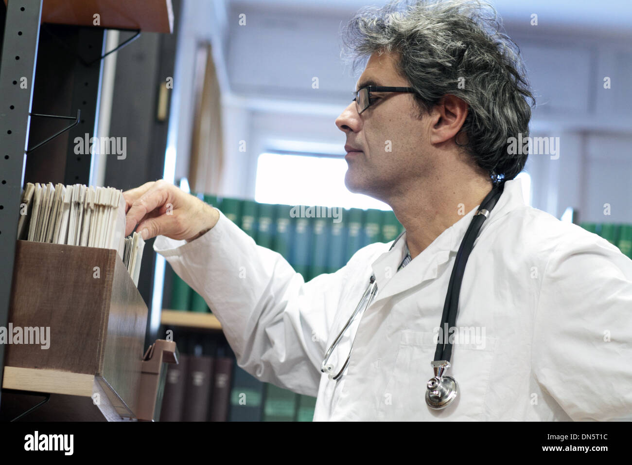 a doctor middle old man caucasian person is standing in a library - Stock Image