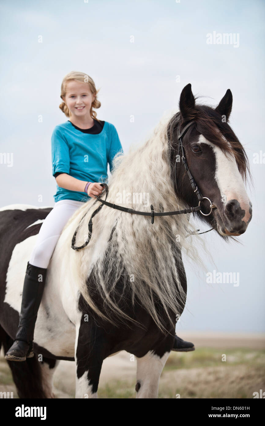 Young horserider riding bareback on a mare, pony, Tinker, black and white chequered, in the dunes at the beach, Borkum - Stock Image