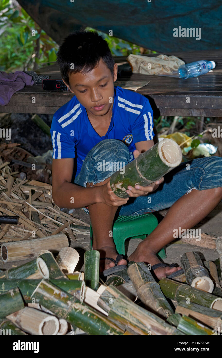 Boy cleaning bamboo tubes used in the preparation of the traditional rice dish Kralan or Khao Lam, Battambang, Cambodia - Stock Image