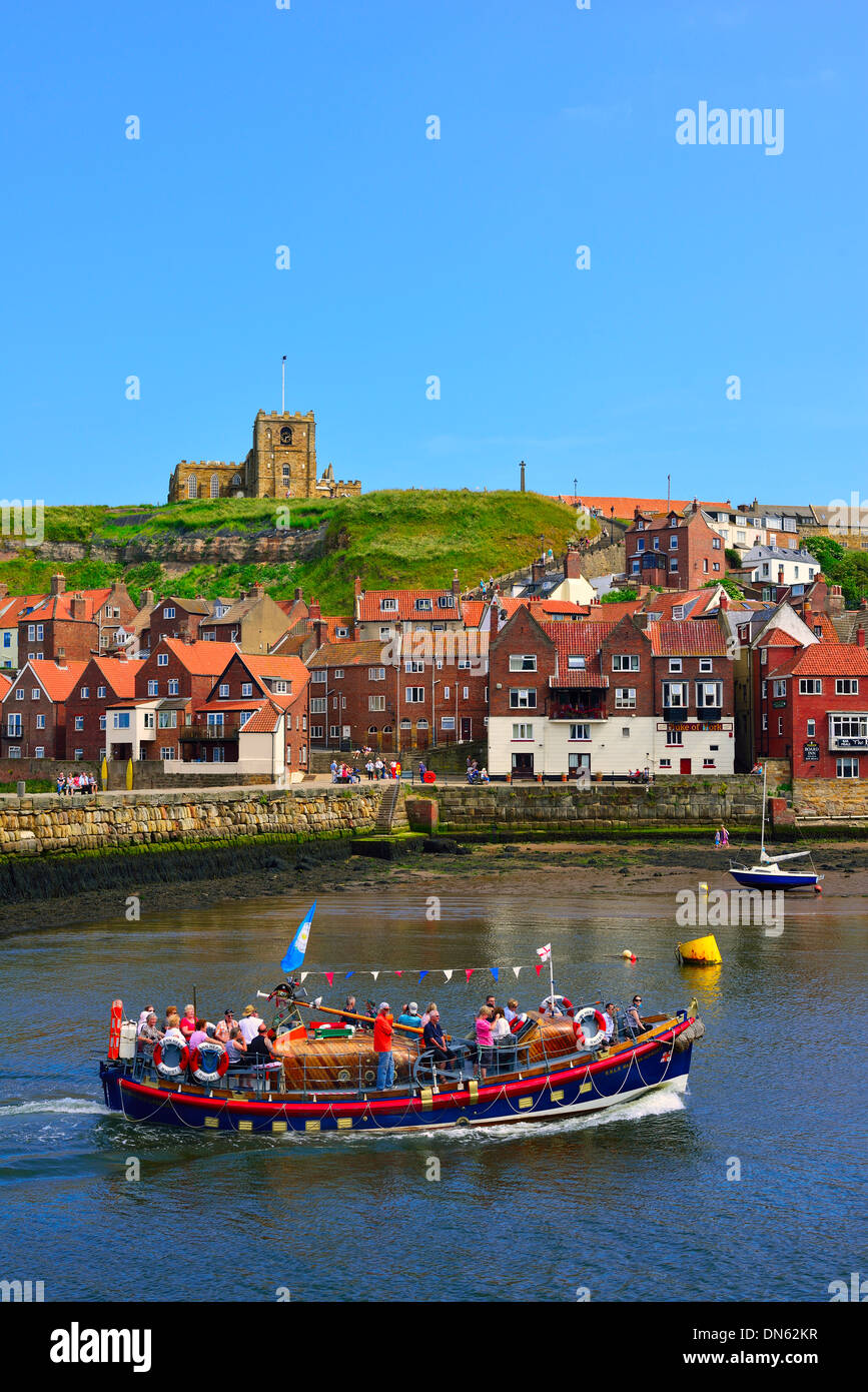 Excursion boat on the River Esk, St. Mary's Church at back, Whitby, North Yorkshire, England, United Kingdom - Stock Image
