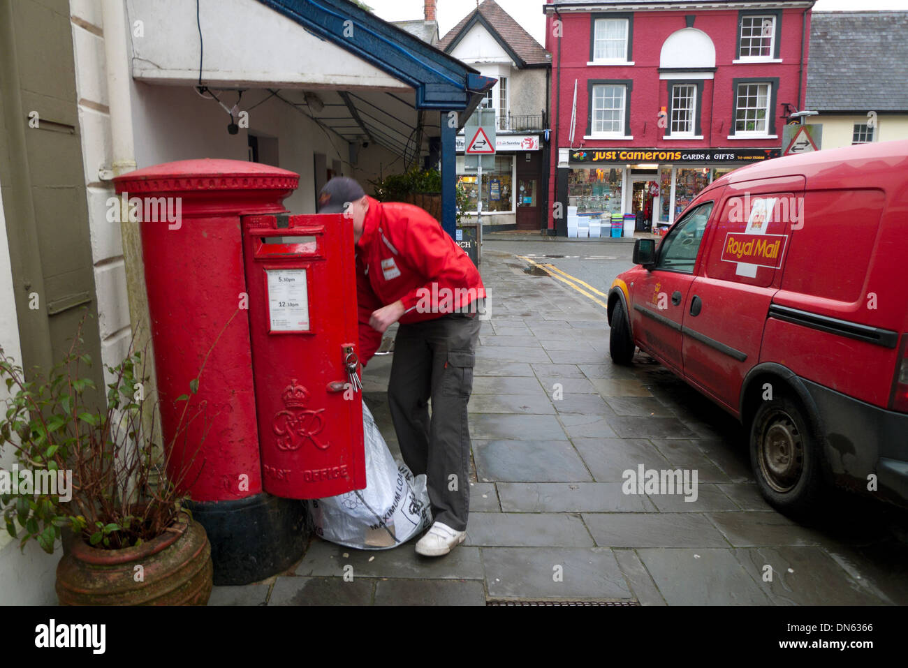 A postal worker emptying mail into a sack from a red postal box next to a Post Office van Llandovery Wales UK   KATHY DEWITT - Stock Image