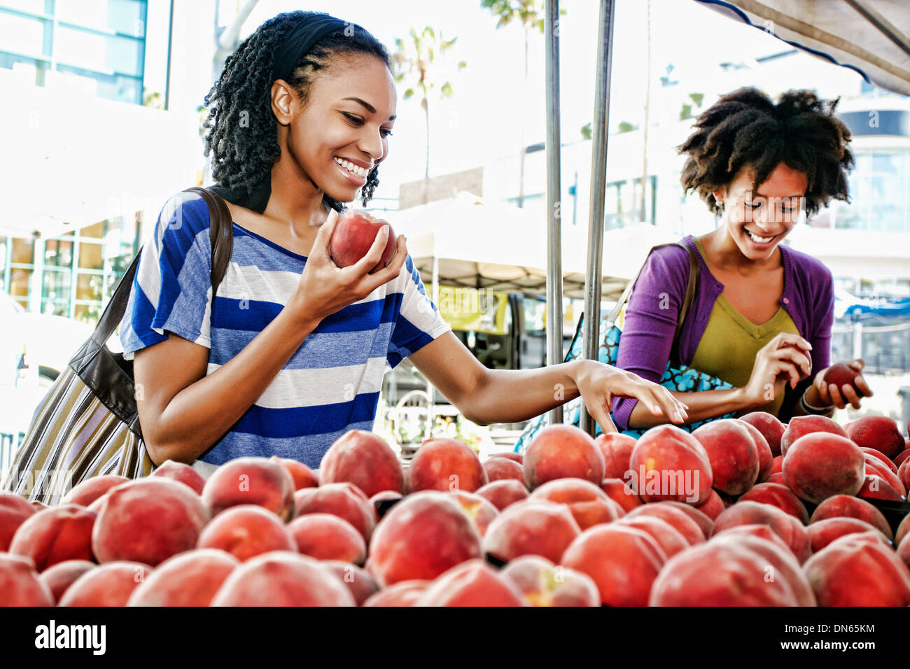 Women shopping together at fruit stand Stock Photo