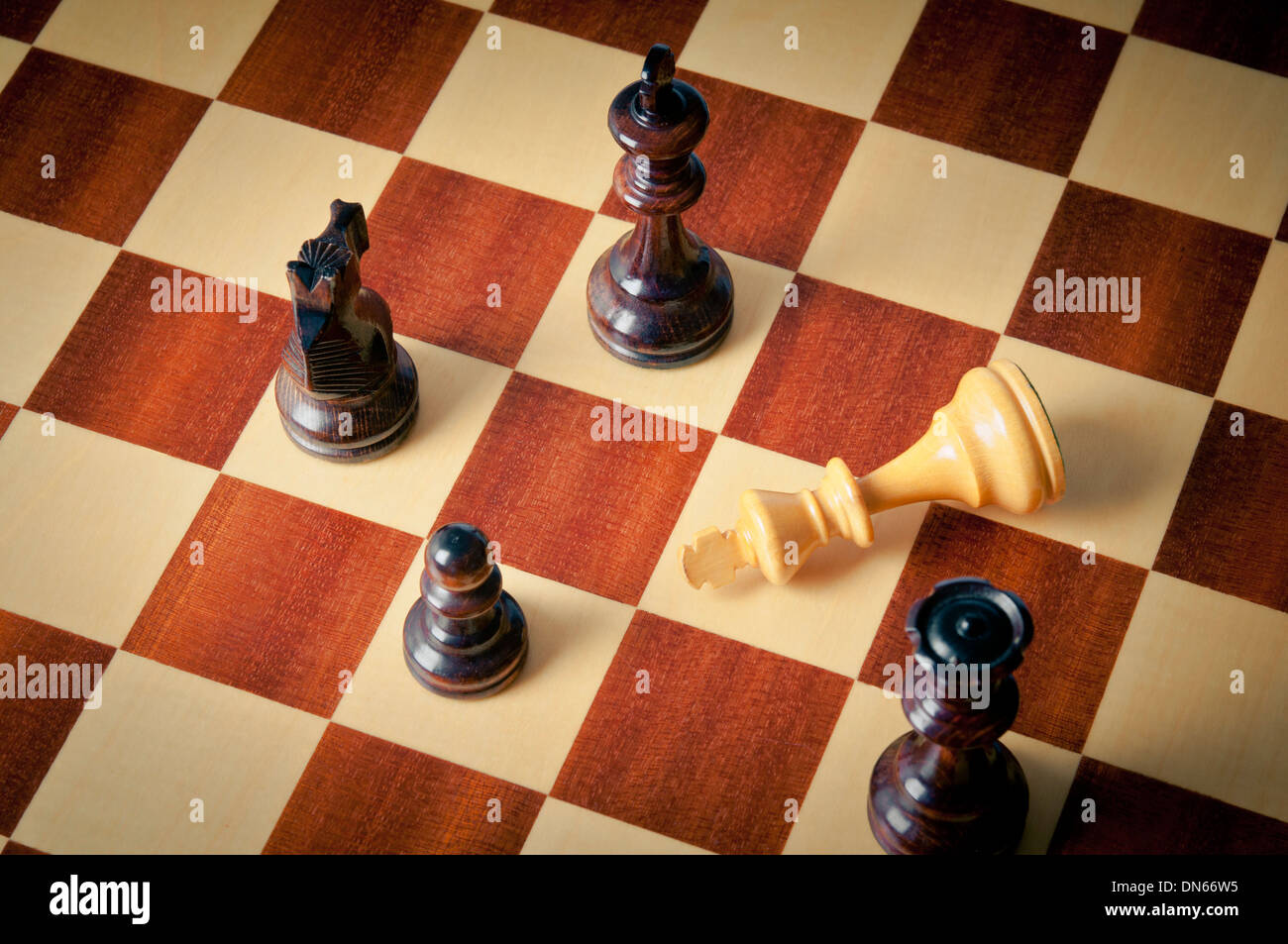 checkmate concept, with white king defeated and surrounded by black pieces - Stock Image