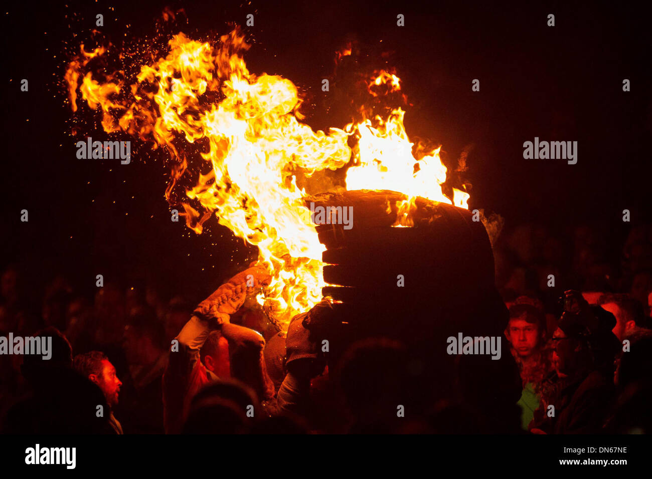 Participants run with a burning tar barrel through the streets of Ottery St Mary, Devon. - Stock Image