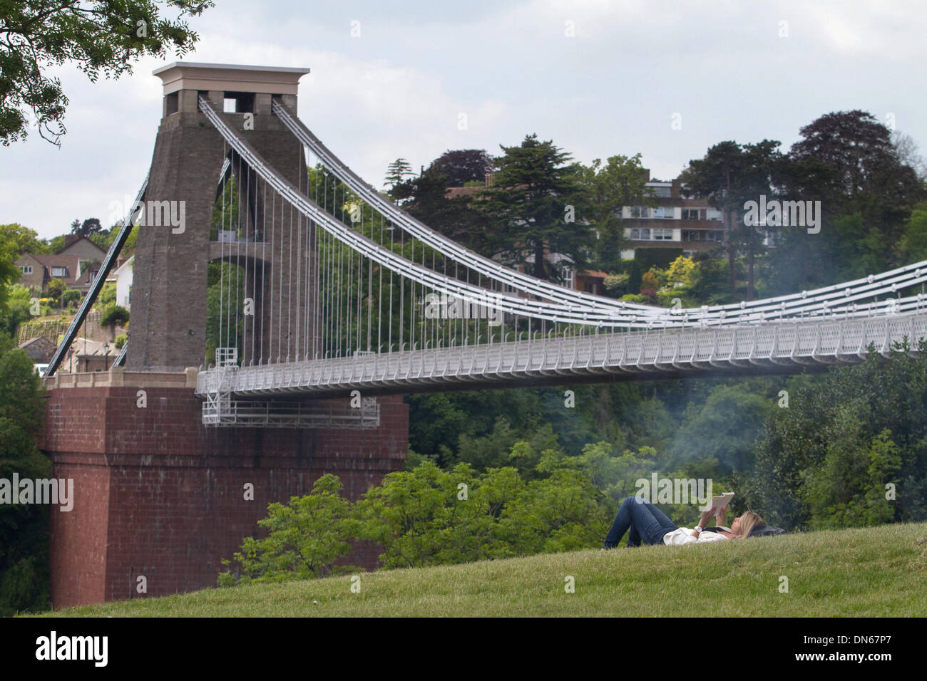 A woman reads in front of Clifton Suspension Bridge, Bristol, as hot weather continues across the UK. 03 June 2013. - Stock Image
