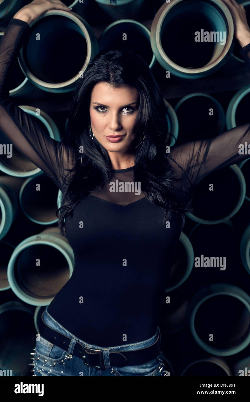 Fashion portrait of woman standing in front of pipes - Stock Image