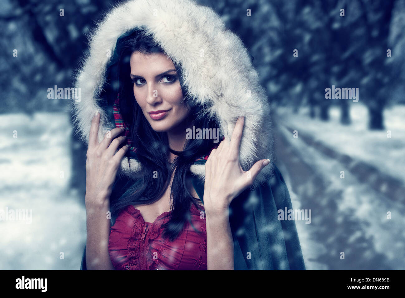 Woman in cape with hood standing on wooded path in the snow - Stock Image