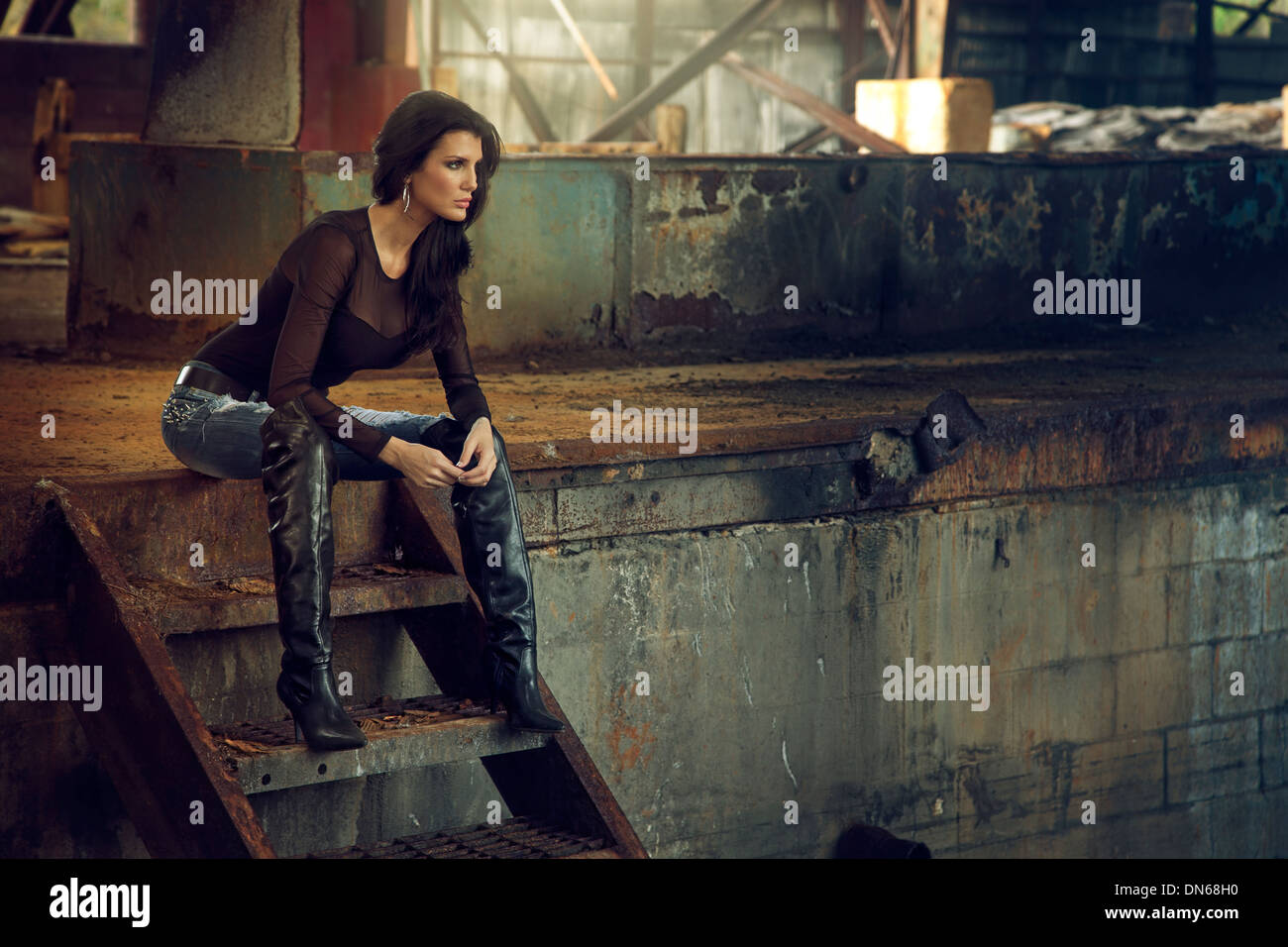 Woman sitting on rusty staircase inside an abandoned warehouse - Stock Image