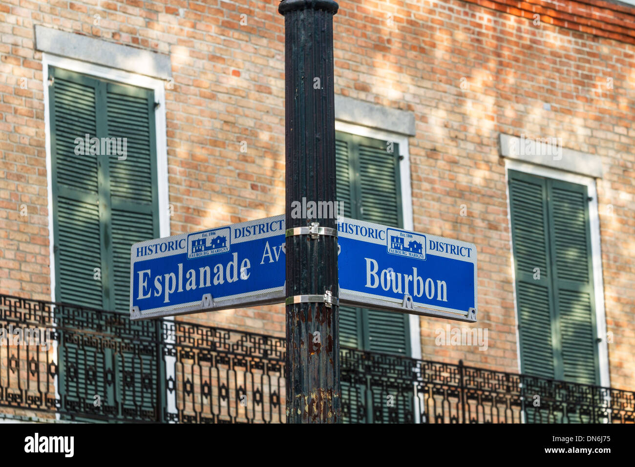 A street sign at the corner of Bourbon St. and Esplanade Ave. against a brick wall in the French Quarter of New Orleans, LA - Stock Image