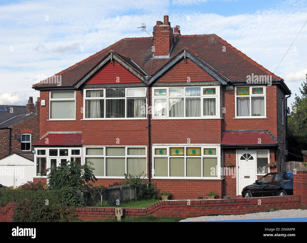 Typical 1930s English brick built semi-detached house with triangles over bedrooms, front garden shared chimney Warrington UK - Stock Image