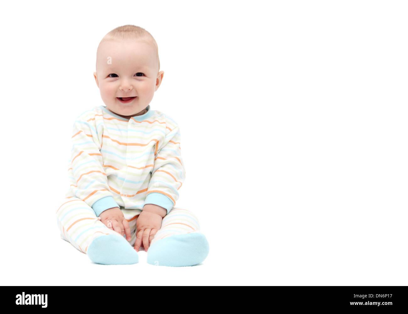 beautiful laughing baby boy sitting on white background - Stock Image
