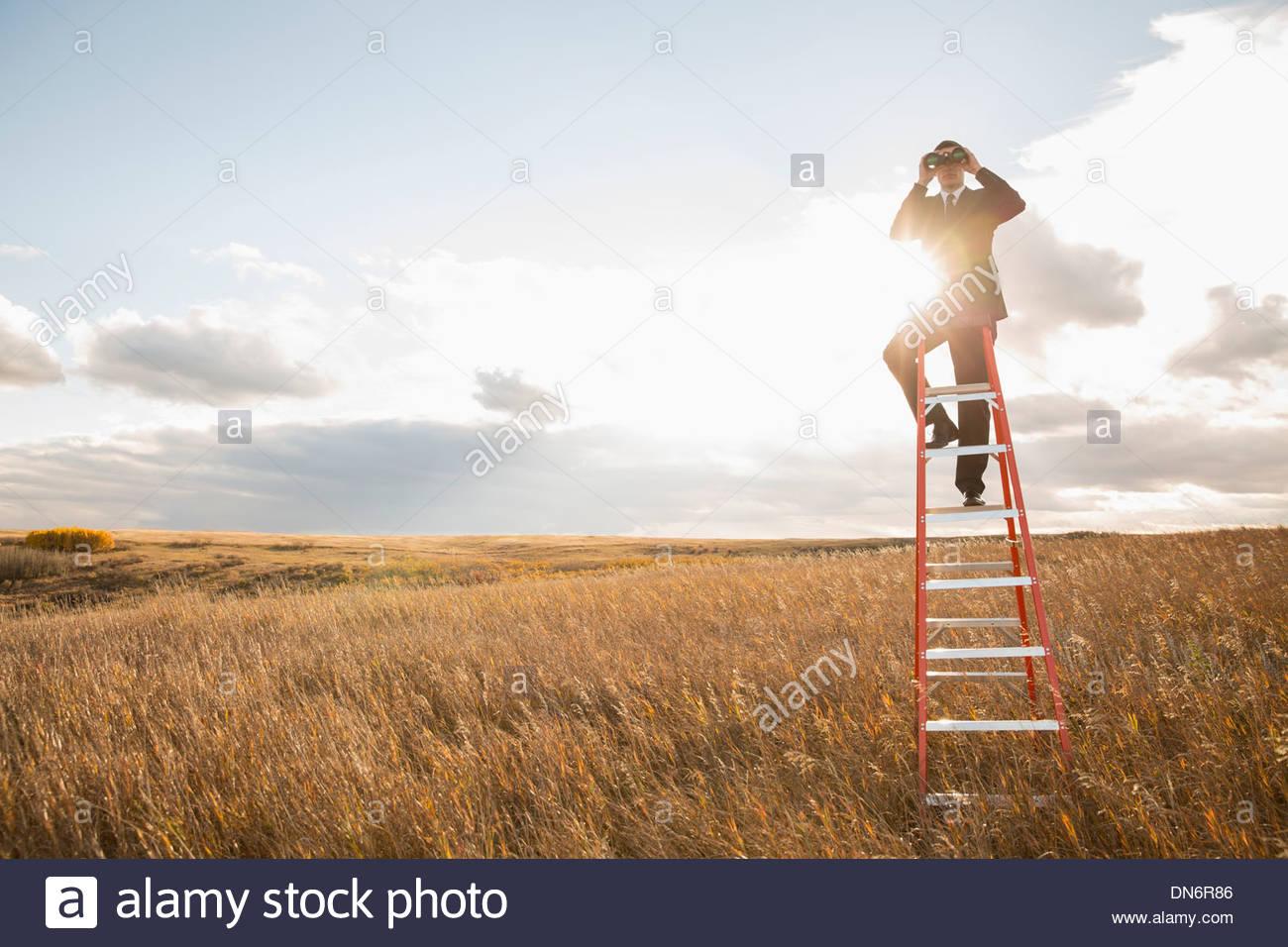 Businessman looking through binoculars on ladder - Stock Image