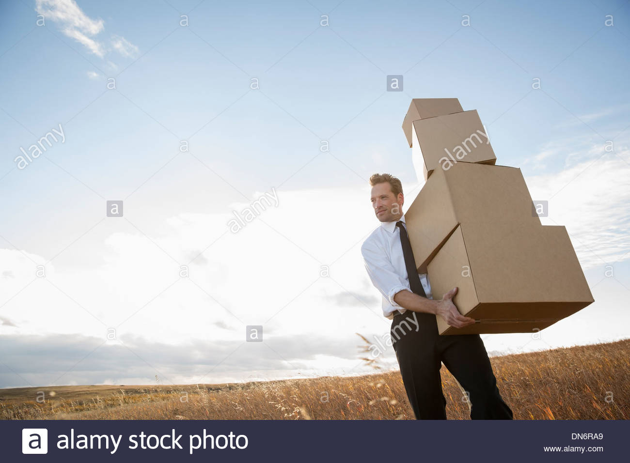 Businessman carrying stacked cardboard boxes - Stock Image