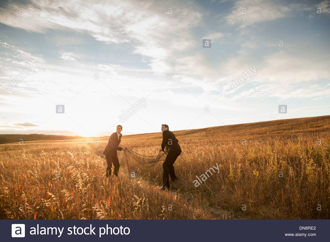 Businessmen throwing fishing net on field - Stock Image