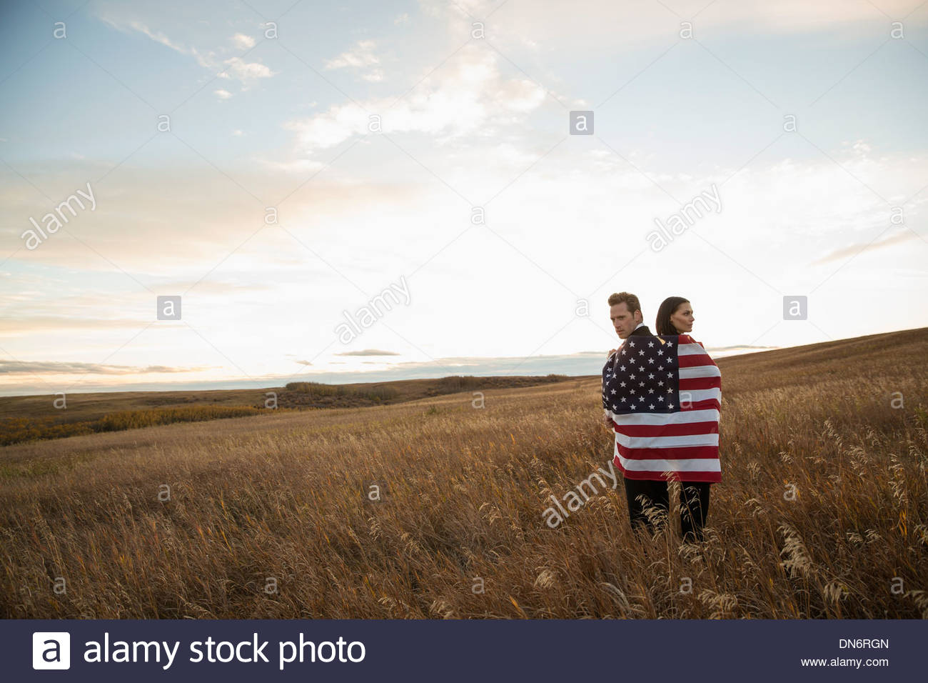 Business colleagues wrapped in American Flag on field - Stock Image