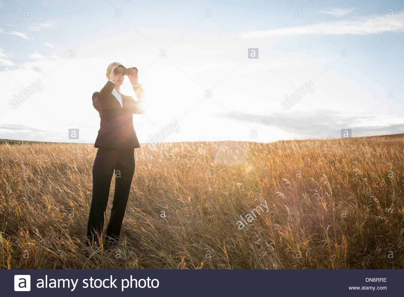 Businesswoman looking through binoculars outdoors - Stock Image