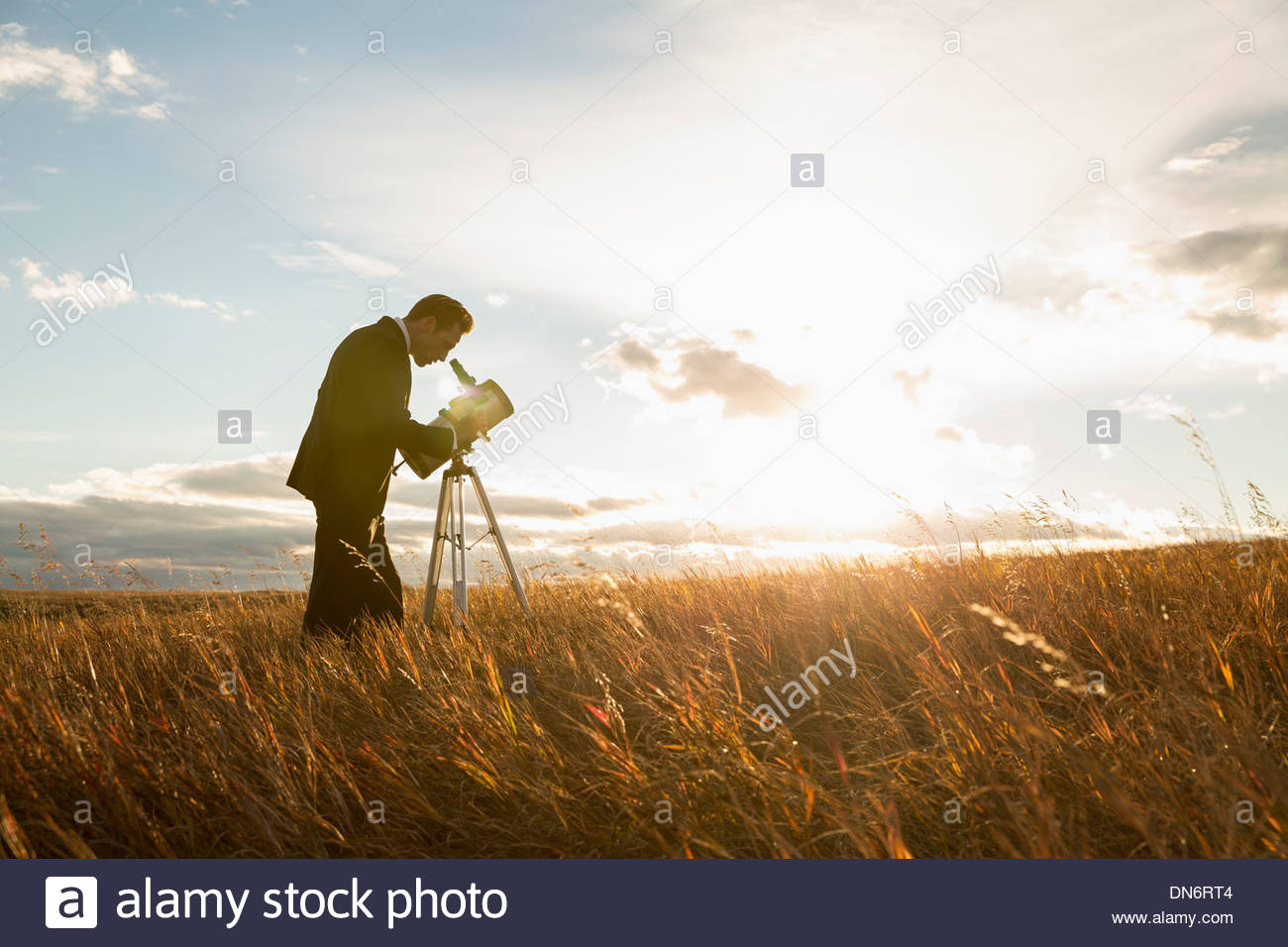 Businessman using telescope on field - Stock Image