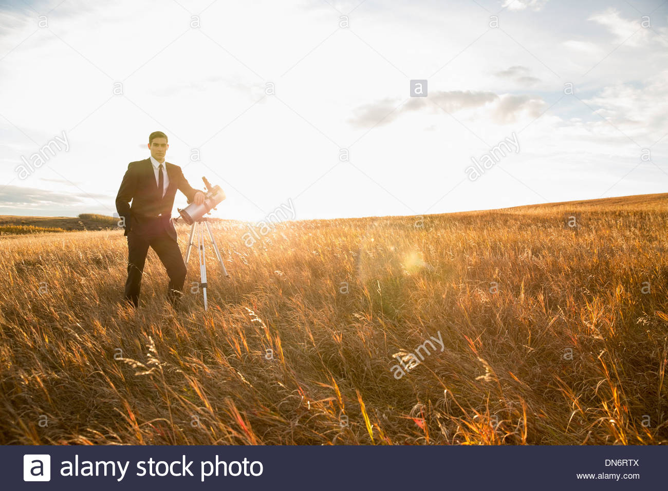 Portrait of confident businessman with telescope on field - Stock Image