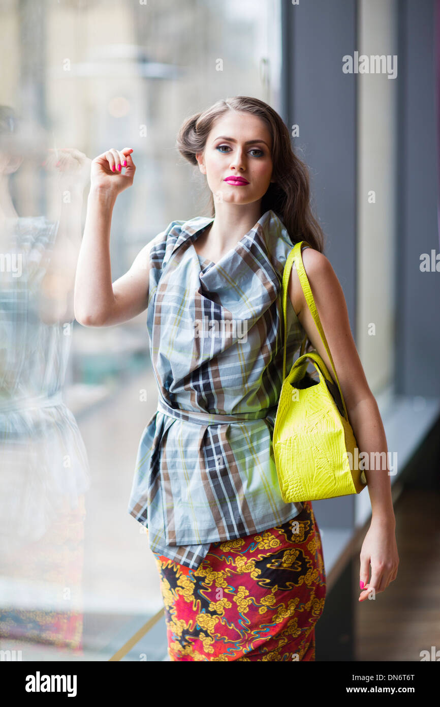 A teenage brunette girl wearing a tartan style top and floral wrap-around skirt with a yellow handbag. - Stock Image