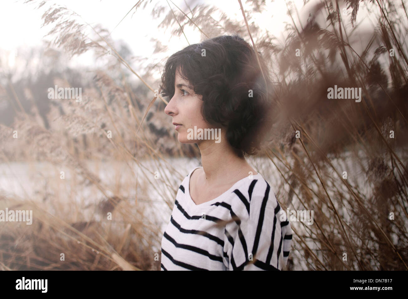 Portrait of a woman between tall grasses in winter - Stock Image