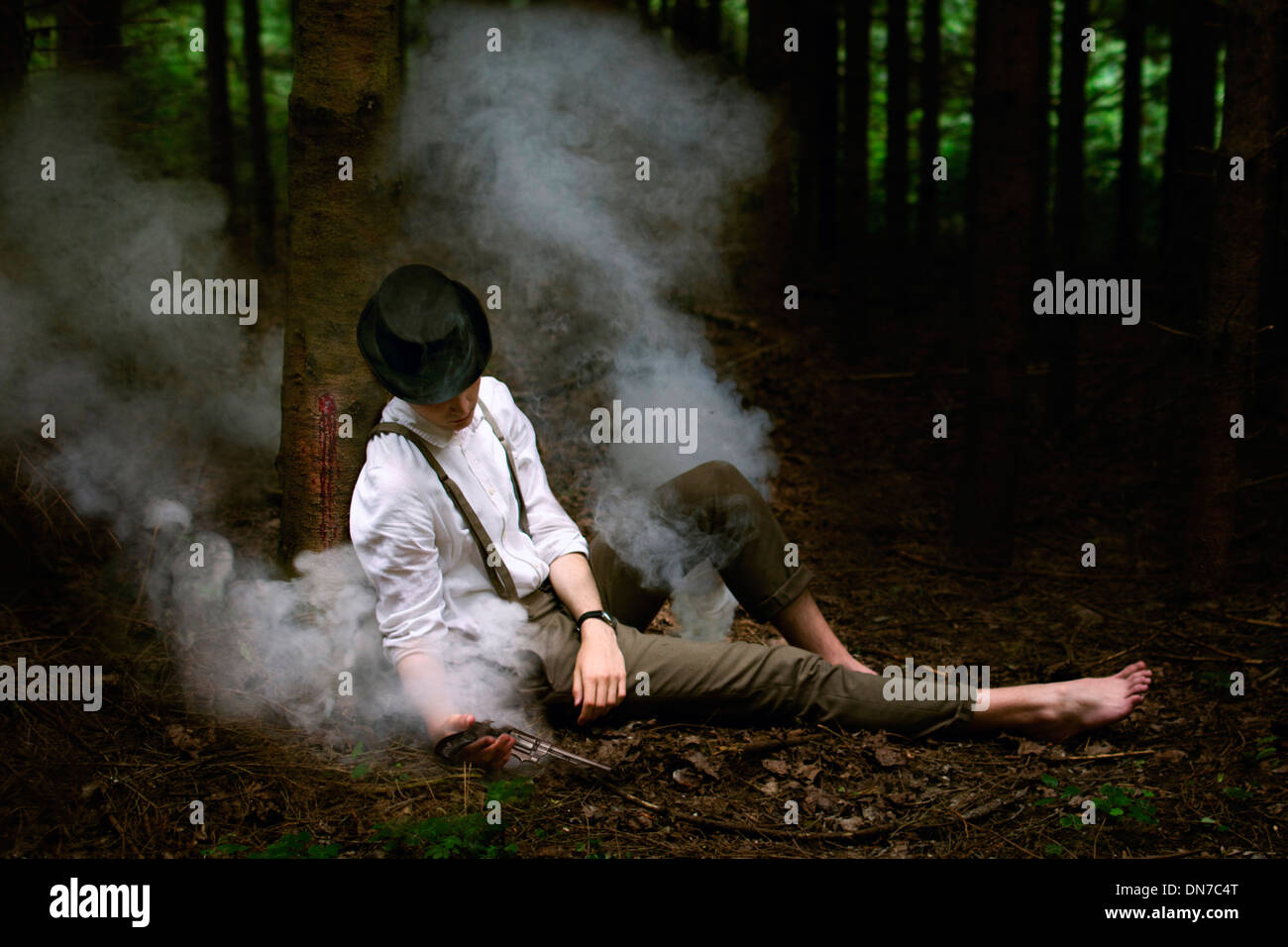 Man surrounded by smoke with gun in hand leaning on tree - Stock Image