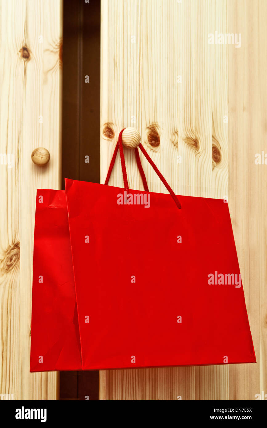 Red shopping bag hanging on wooden cabinet door. - Stock Image
