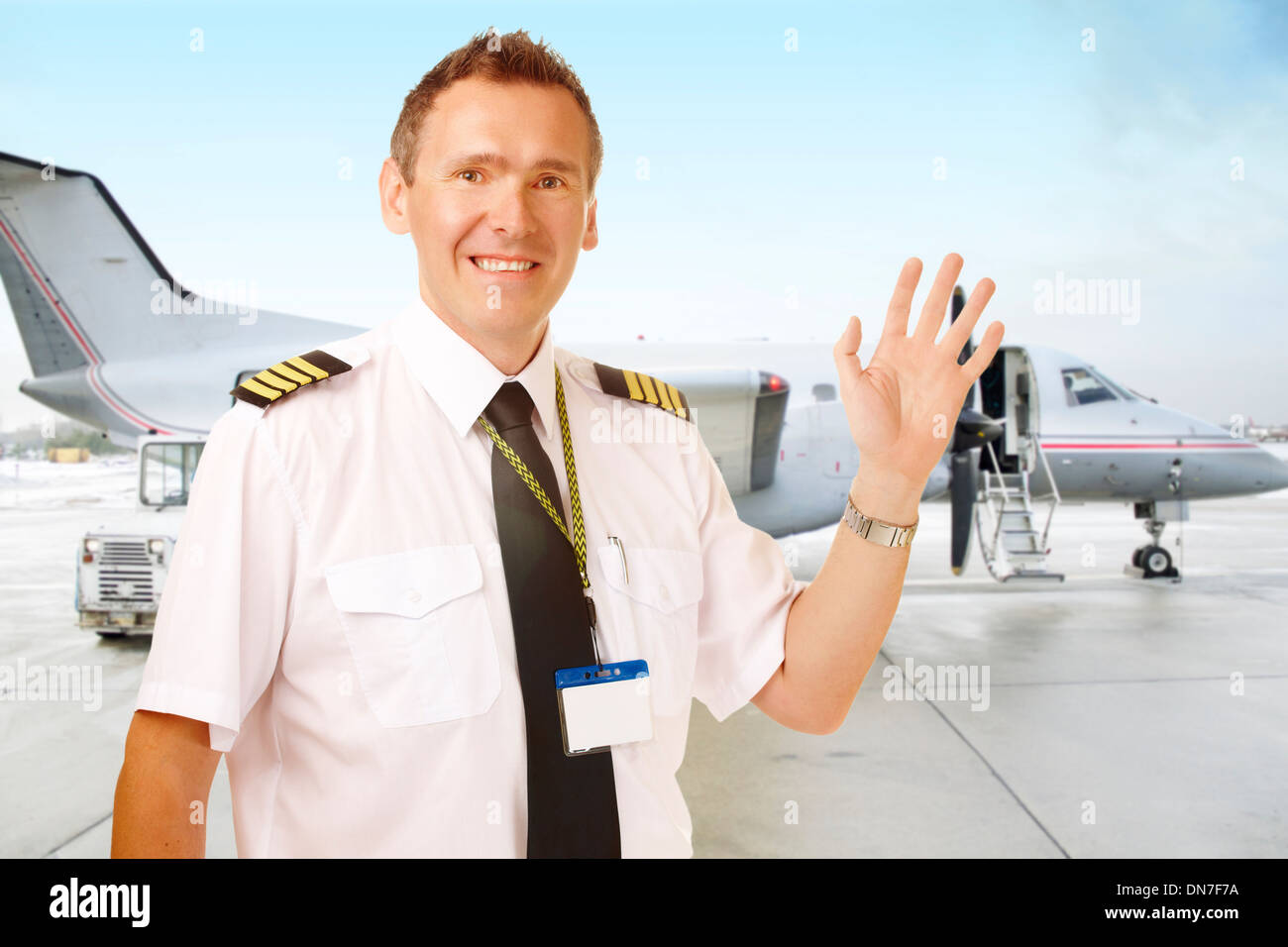 Airline pilot wearing uniform with epaulettes waving, with passenger aircraft in background - Stock Image
