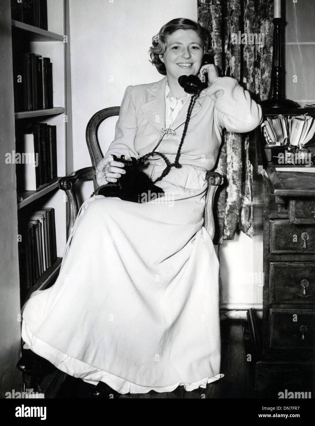Nov. 24, 1953 - London, England, U.K. - Wife of Captain A.C. Loraine, MARY LORAINE still wearing her nightgown and housecoat uses the telephone to tell a friend the police have sealed her bedroom to search for clues after a large robbery. - Stock Image