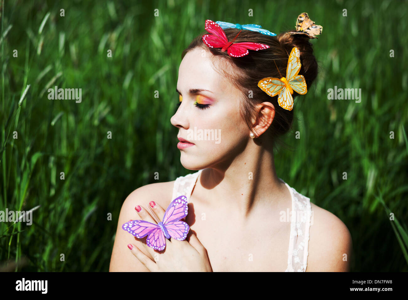 Young woman with closed eyes and artificial butterflies - Stock Image