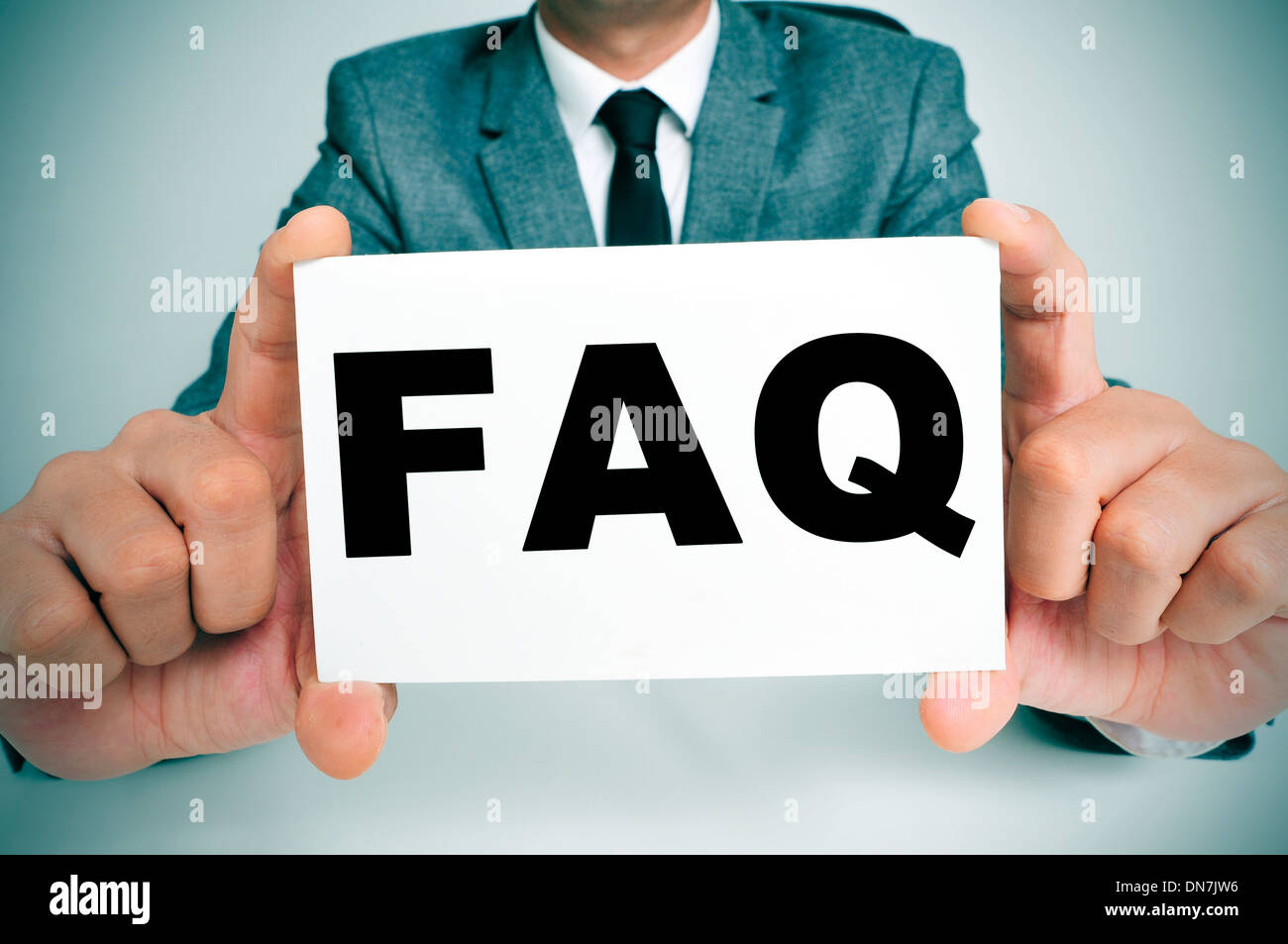 a man wearing a suit sitting in a desk holding a signboard with the word FAQ, Frequently Asked Questions, written in it - Stock Image