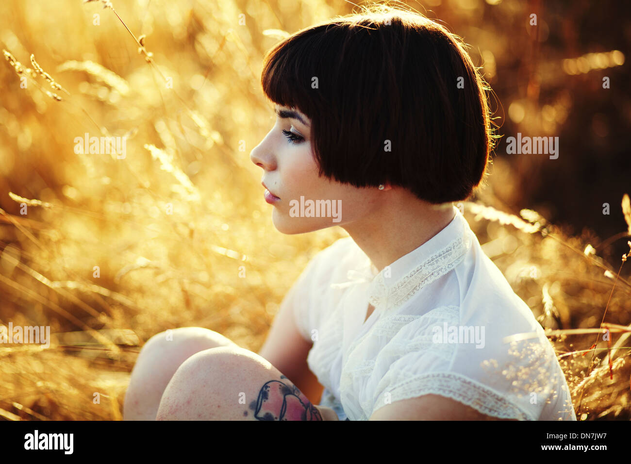 Young woman sitting on a meadow, portrait - Stock Image