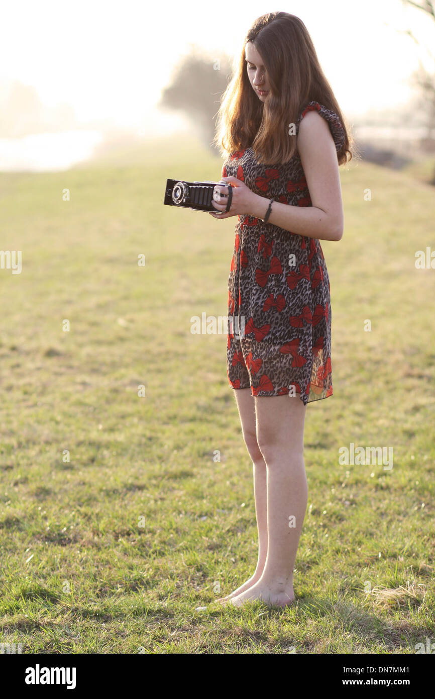 Young woman on a meadow with nostalgic camera - Stock Image