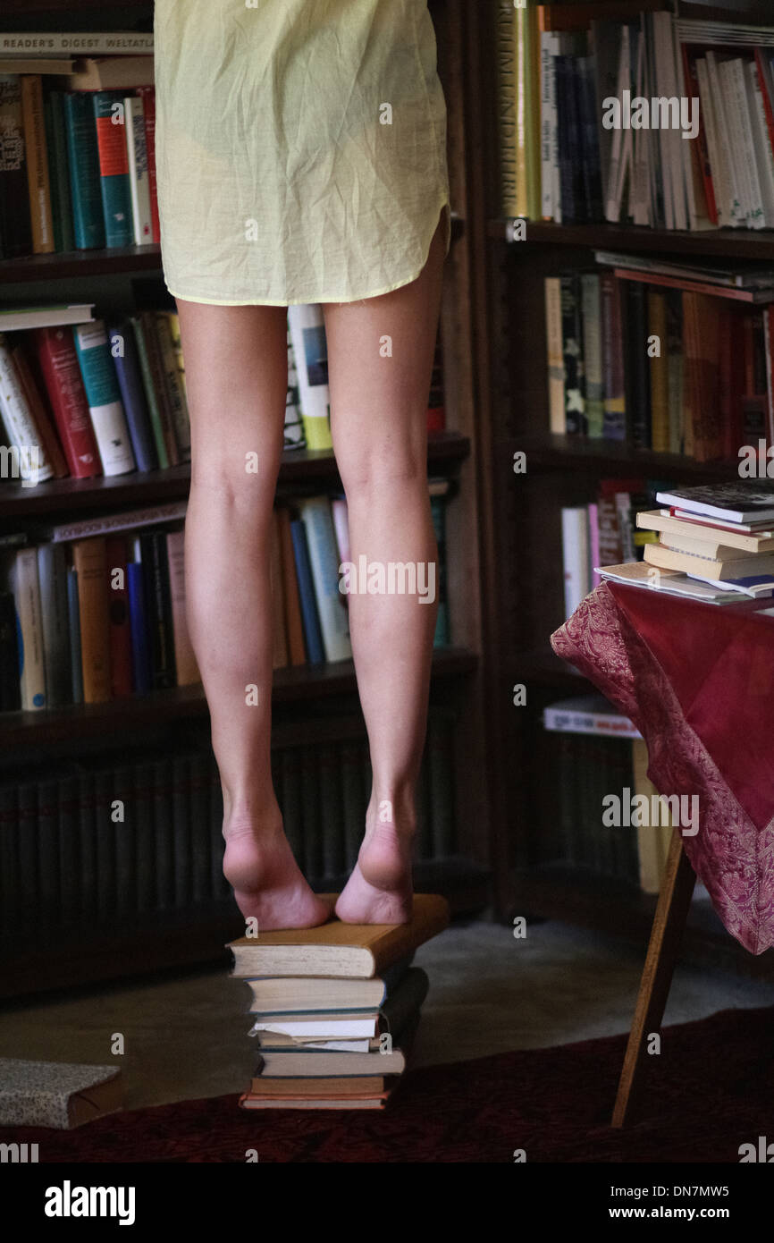 Woman standing on stack of books in front of bookshelf - Stock Image