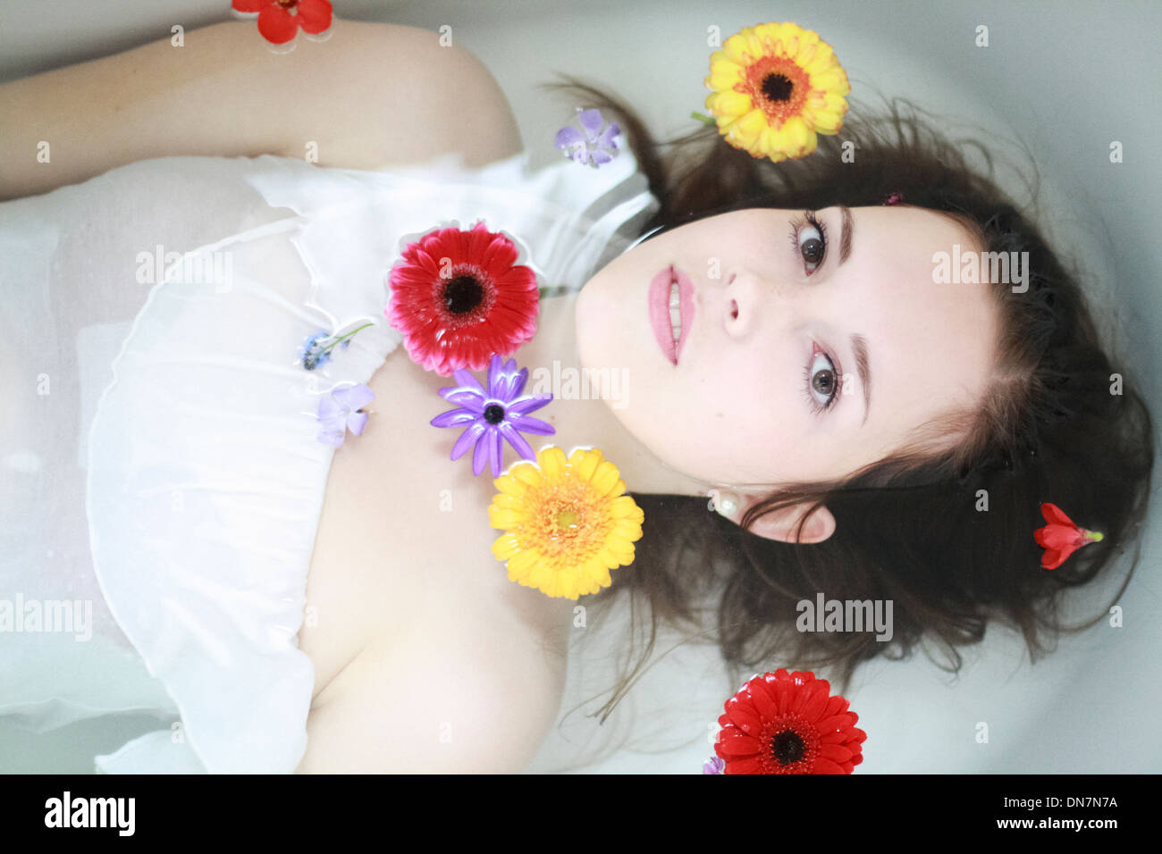 Young woman with flowers in the bathtub Stock Photo
