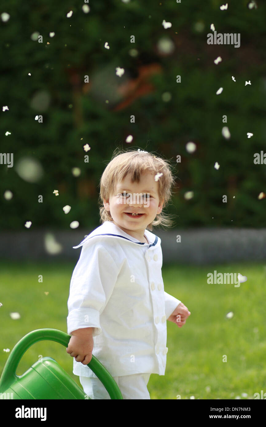 Little boy with watering can on a meadow - Stock Image