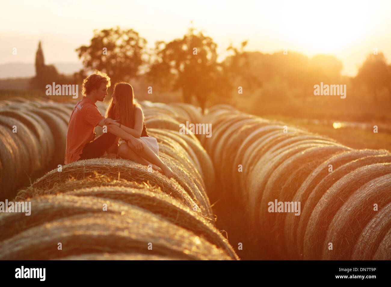 Loving couple sitting on hay bales in backlight - Stock Image