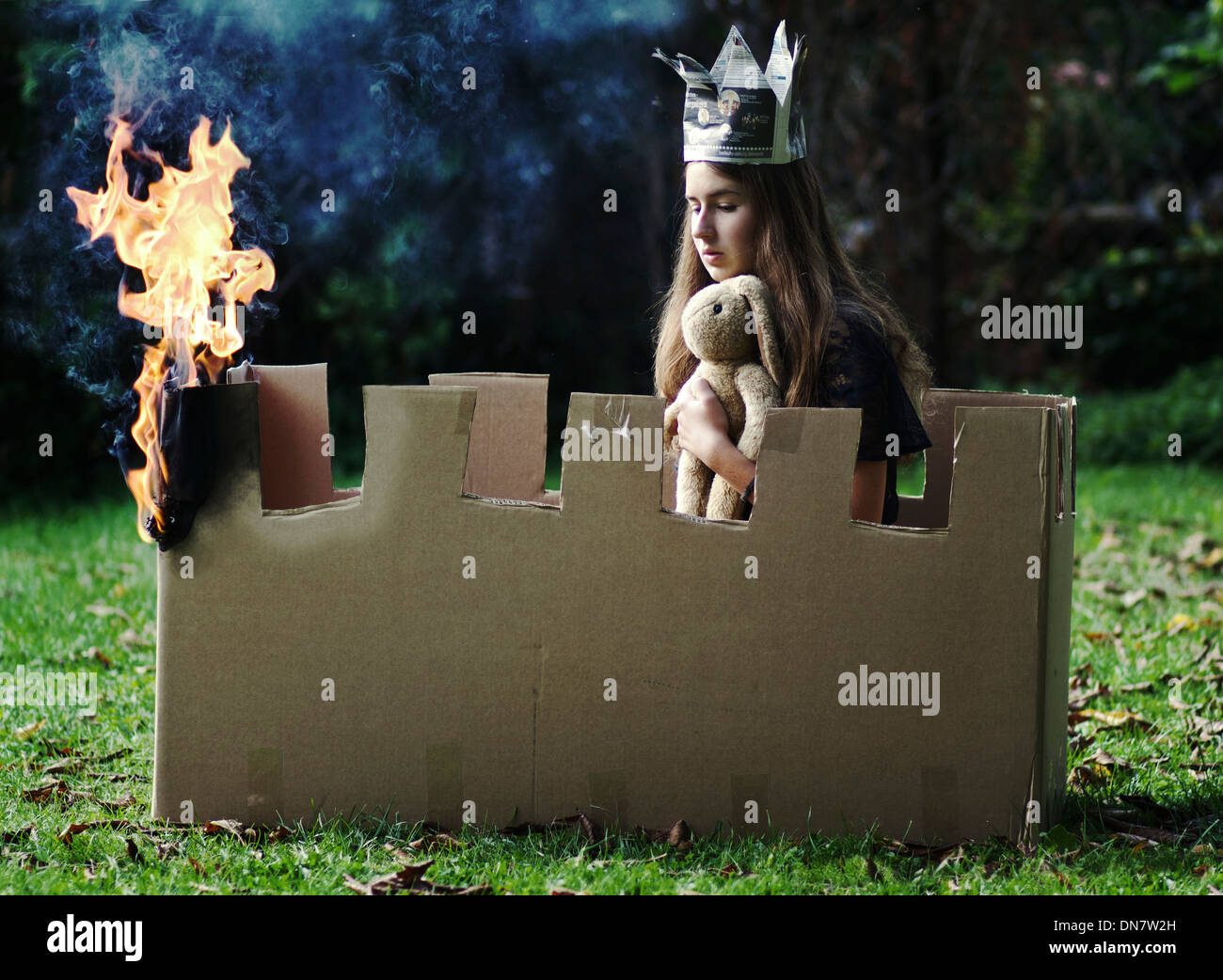 Young girl with plush toy and paper crown sits in a burning castle made of cardboard - Stock Image