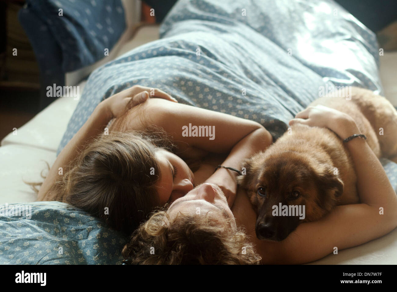 Loving couple lying in bed with dog - Stock Image