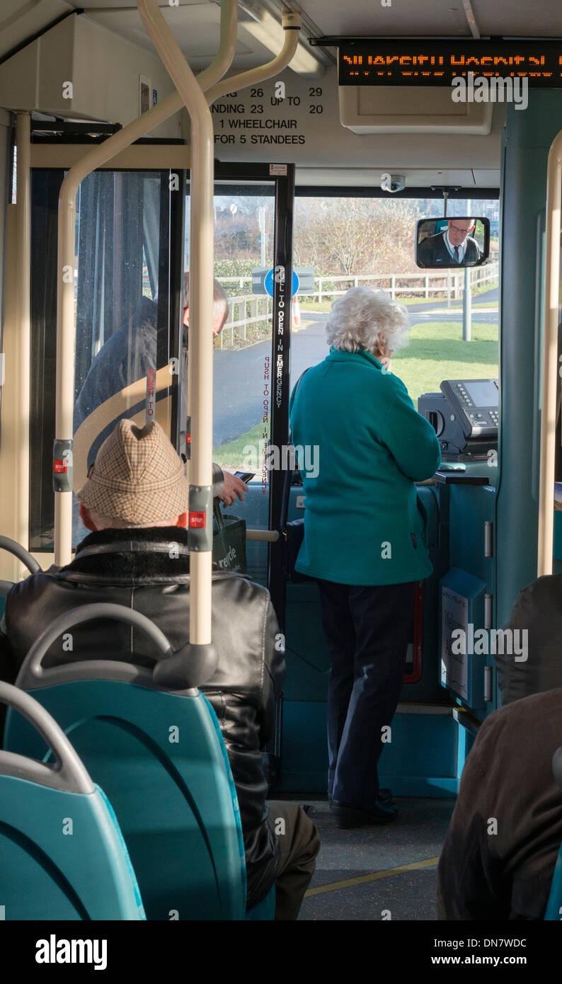 Senior Citizen boarding a bus. - Stock Image