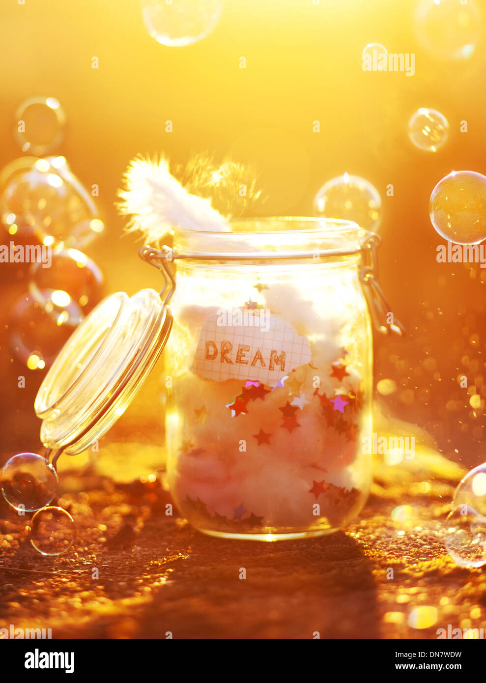 Preserving jar with paper, feathers and bubbles in backlight - Stock Image