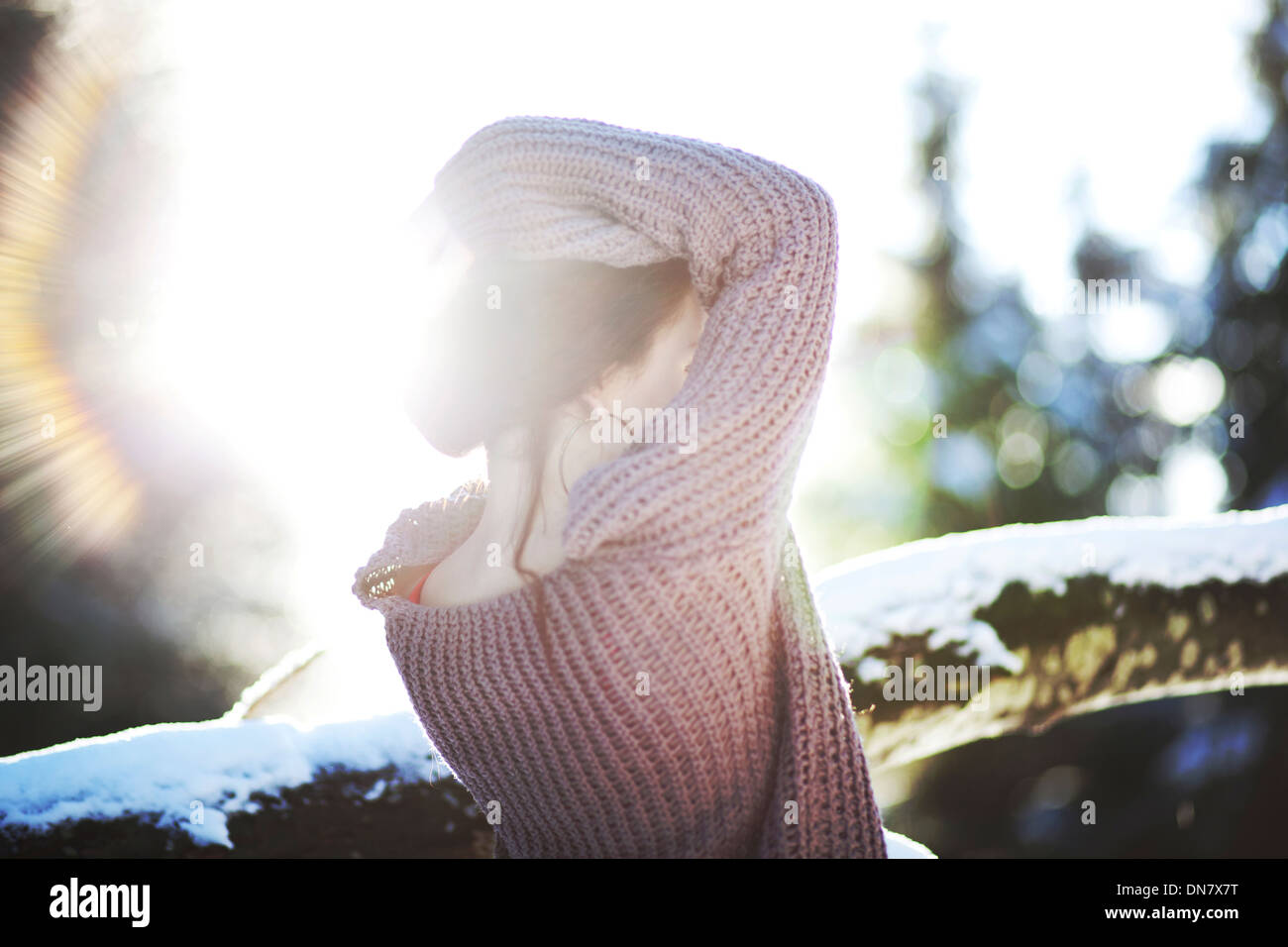 Portrait of a young woman in the snow in backlight - Stock Image