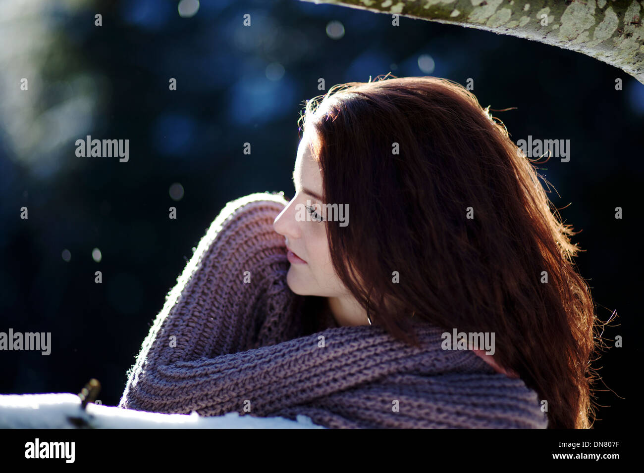 Young woman lying on a tree trunk in snow - Stock Image