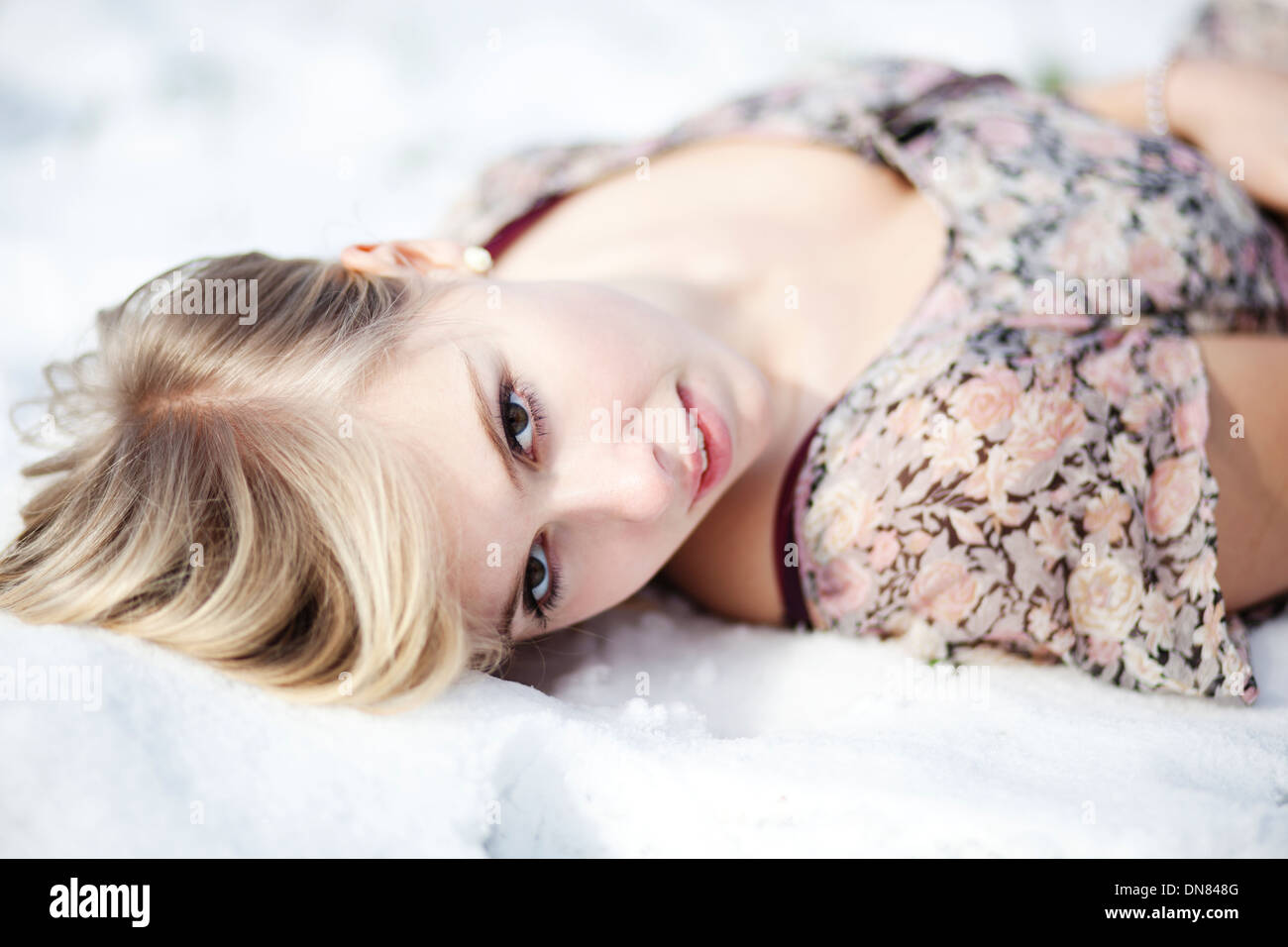 Young woman lying in snow, portrait - Stock Image